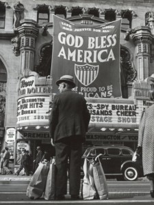 bob-landry-man-with-shopping-bags-in-front-of-million-dollar-theatre-emblazoned-with-god-bless-america-banner